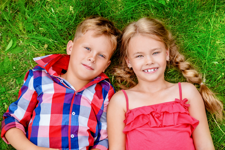 Photo for Children are lying on the grass in the countryside. Fashion, beauty. Summer. - Royalty Free Image