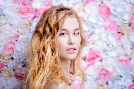 Photo pour Beautiful romantic young woman with natural makeup posing on a background of roses. Perfume, cosmetics concept. - image libre de droit