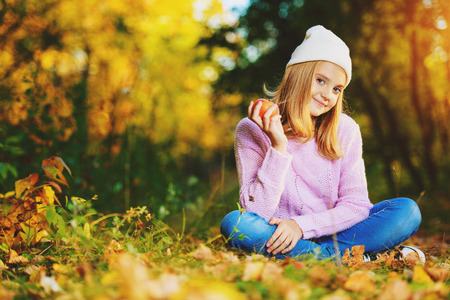 Foto de A pretty young girl is sitting on the ground with golden leaves and holding an apple. Autumn fashion, beauty. Healthy lifestyle. - Imagen libre de derechos