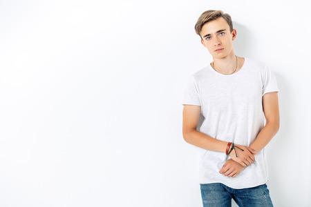 Photo pour A portrait of a young goodlooking guy in a white t-shirt. Beauty of men, casual fashion. - image libre de droit