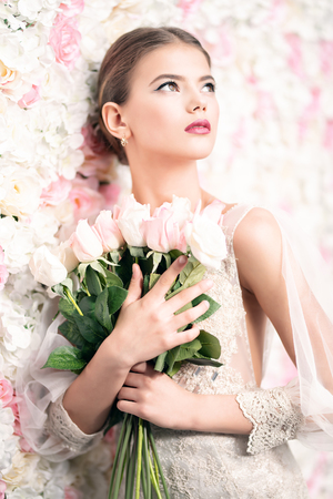 Photo for A portrait of a dreamy lady in a wedding dress posing indoor with flowers. Wedding, beauty, fashion. - Royalty Free Image