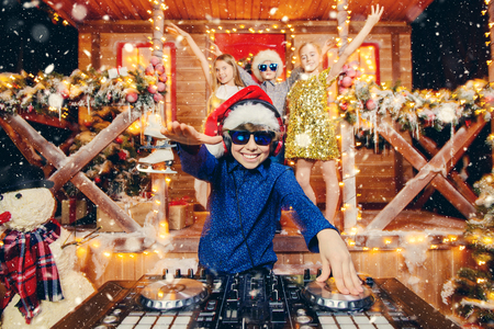 Photo pour Group of happy children is having a party near the house of Santa Claus decorated with lights. Christmas party concept. - image libre de droit