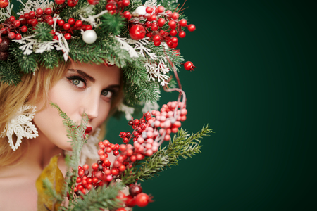 Photo pour Christmas winter beauty woman. Charming blonde girl with Christmas decoration on her head holds a New Year's bouquet with mistletoe and smiles. Studio portrait over green background. Copy space. - image libre de droit