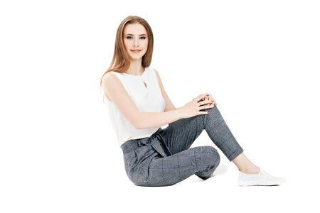 Foto de A portrait of a beautiful dark-haired girl sitting in the studio over the white background. Beauty, formal fashion. - Imagen libre de derechos