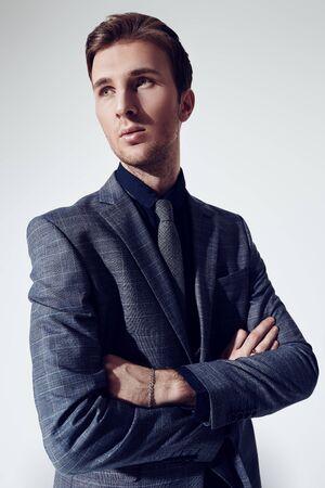 Foto de A portrait of a handsome young businessman in a formal suit at studio. Men's fashion. - Imagen libre de derechos