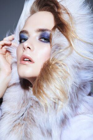 Photo pour A close up portrait of a beautiful woman wearing a fur coat with hood. Beauty, winter fashion, style. - image libre de droit