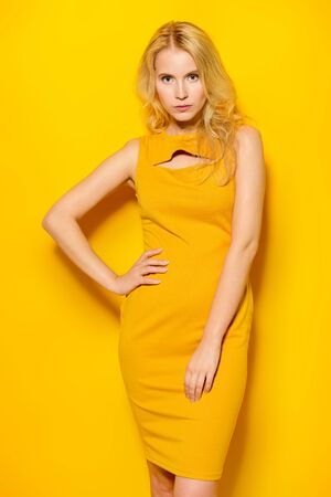 Photo for Beauty, fashion shot. Beautiful slender girl in a yellow dress on a yellow background. Blonde hair. - Royalty Free Image