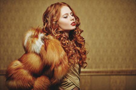 Foto de Fur coat style. Portrait of a beautiful sensual woman with red hair in a luxurious fox fur coat. Winter beauty fashion. - Imagen libre de derechos