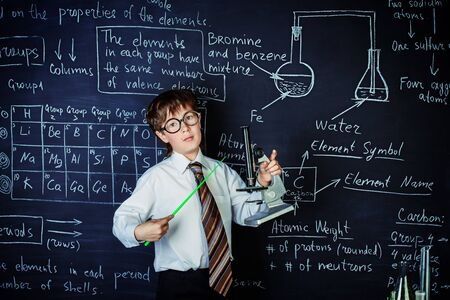 Photo for Serious schoolboy answering by a blackboard on a chemistry lesson. Educational concept. - Royalty Free Image