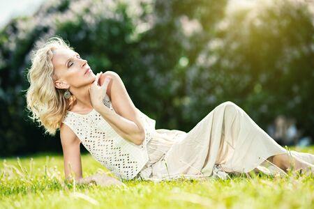 Photo pour A portrait of an elderly woman relaxing on the grass in the summer park. Beauty, healthcare. - image libre de droit