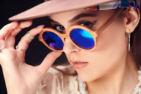 Photo for Portrait of a modern girl wearing hat and sunglasses on a black background. Summer fashion. Boho, modern hippie style. - Royalty Free Image