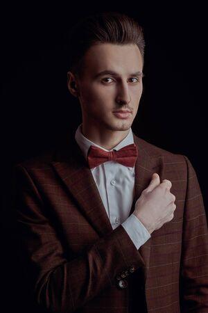 Photo pour Portrait of a handsome man in elegant classic suit and bow tie on a black background. Business style. Men's fashion. - image libre de droit