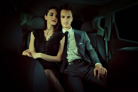 Photo for Fashionable couple of young people in the car. Glamorous lifestyle, night party. - Royalty Free Image