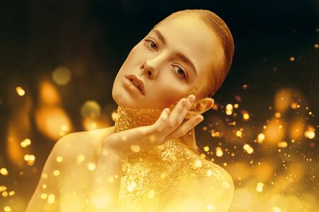 Photo for Beauty, fashion gold concept. Portrait of a beautiful girl model with golden skin and golden make-up on on a sparkling and black background with golden lights. Jewelry. Cosmetics and beauty care. - Royalty Free Image