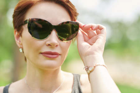 Photo for Happy middle-aged woman in modern sunglasses in summer park. Close up portrait. - Royalty Free Image