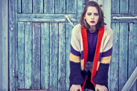 Photo pour Modern stylish girl stands by the old wooden wall in the city. Fashion model, autumn style. - image libre de droit