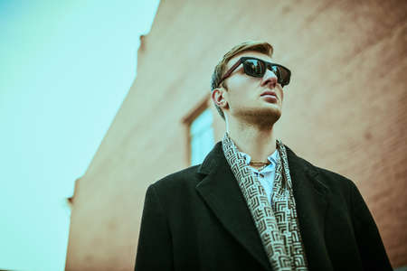 Photo pour Urban men's style. Handsome man in black sunglasses and elegant black coat stands against the background of the grunge brick houses of the big city. - image libre de droit