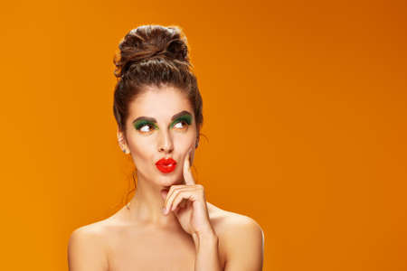Photo pour Portrait of an attractive playful girl with colorful makeup posing coquettishly on a orange background. Makeup and cosmetics. Studio shot. Copy space. - image libre de droit