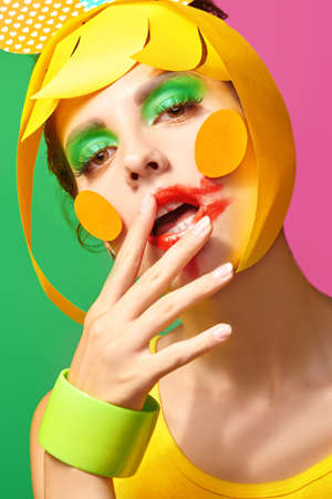 Photo pour Bright make-up and cosmetics. Close up portrait of a fashionable beauty girl with colorful paper makeup and hairstyle and smudged lipstick on green and fuchsia background. - image libre de droit
