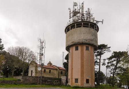 Foto per torre in cemento di acquedotto in ambiente naturale usata come base per impianti di telefonia mobile e televisivi - Immagine Royalty Free