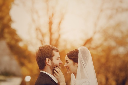 Happy couple whose wedding photo shoot in a golden autumn