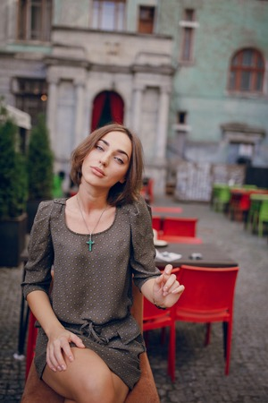 beautiful young model sitting in a cafe on the street