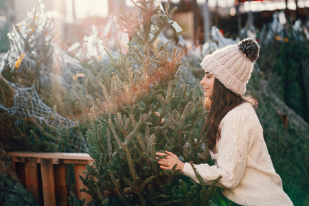 Foto per Cute brunette in a white sweater with Christmas tree - Immagine Royalty Free