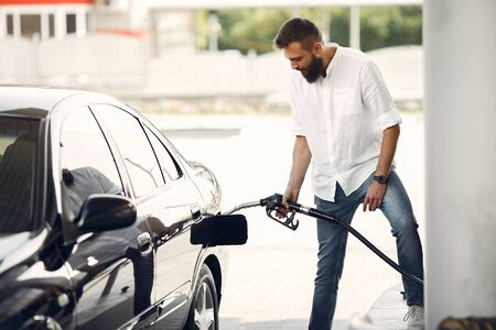 Photo for Handsome man pours gasoline into tank of car - Royalty Free Image