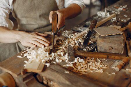 Photo pour Man working with a wood. Carpenter in a white shirt - image libre de droit