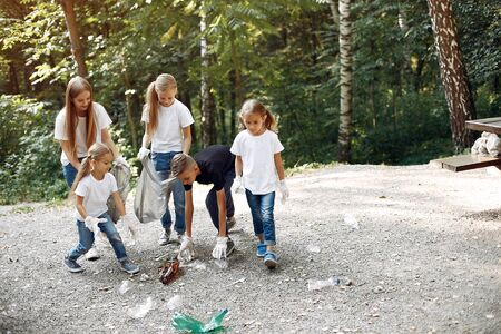 Photo pour Children collects garbage in garbage bags in park - image libre de droit
