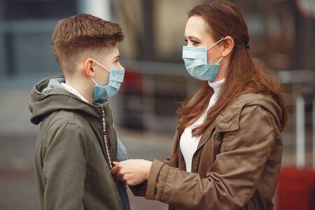 Photo pour A boy and mother are wearing protective masks - image libre de droit