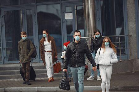 Photo pour Travelers leaving airport are wearing protective masks - image libre de droit