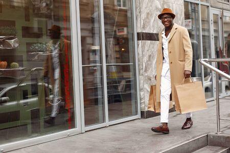 Photo pour Stylish black man in a city with shopping bags - image libre de droit