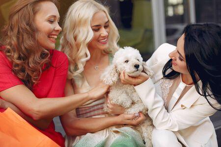 Photo pour Three elegant women with little dog in a city - image libre de droit
