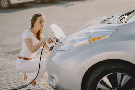 Photo for Woman charging electro car at the electric gas station - Royalty Free Image
