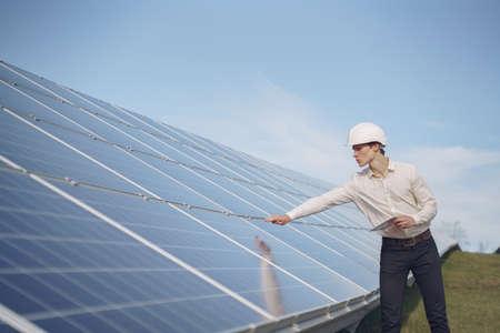 Photo pour Businessman in a white helmet near solar battery - image libre de droit