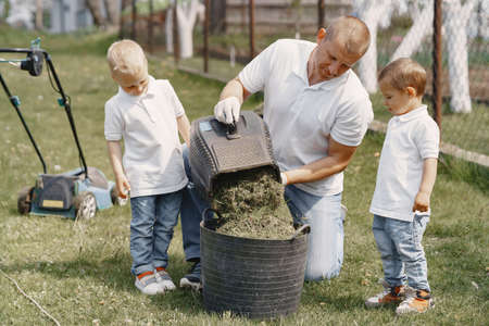 Photo pour lawn mower man working on the backyard with sons - image libre de droit