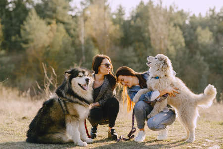 Photo pour Women in a spring forest. Girls with cute dogs. Stylish friends walks. - image libre de droit