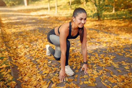 Photo pour Sports girl in a black top training in a autumn park - image libre de droit