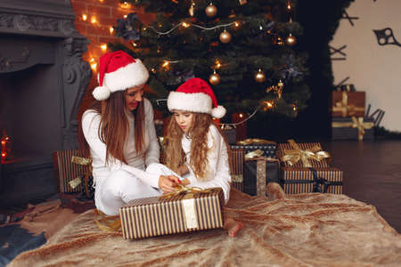Photo for Mother with cute daughter at home near fireplace - Royalty Free Image
