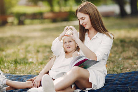 Photo pour Mother with little daughter sitting on a plaid and read the book - image libre de droit