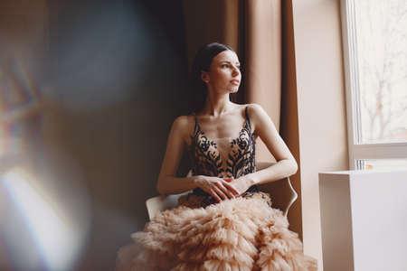 Foto de Beautiful woman model posing in elegant dress in the studio - Imagen libre de derechos