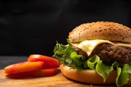 Photo for fresh tasty homemade hamburger with fresh vegetables, lettuce, tomato, cheese beside sliced tomatoes on a cutting board. Free space for text - Royalty Free Image