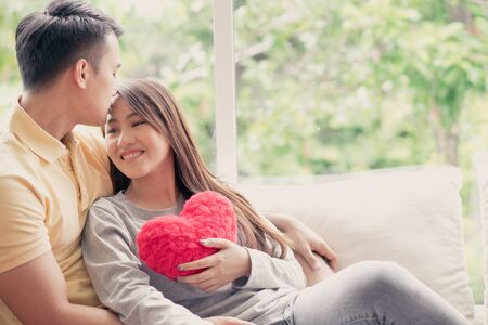 Photo pour Asian Couples Sitting on the sofa In which women Holding a red heart And smiling happily. Concept of expressions of love and warmth for lovers, Valentine day. - image libre de droit