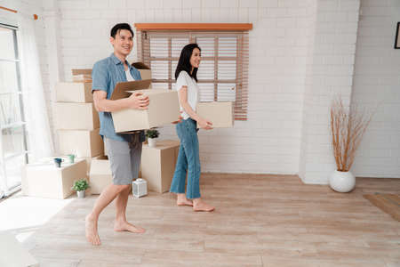 Happy young couple Carrying cardboard boxes and walking from the front door into the house in a new house at moving day. Concept of relocation, rental, and homeowner moving at home.
