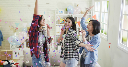 carefree best friends having fun together at home birthday party. group of friends playing whistles blowing cheerfully dancing indoors. decorated house with colorful confetti celebration.の写真素材
