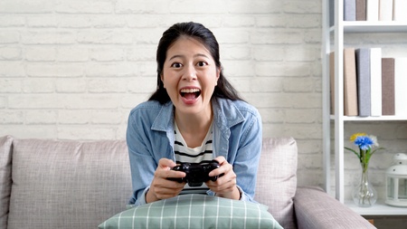 cheerful woman holding the toy controller playing video game at home. young asian girl enjoy excited having fun sitting in sofa in living room at apartment. housewife in daytime leisure lifestyle.の写真素材