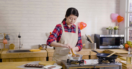 Foto de pretty asian woman wear apron standing by the stove in wooden kitchen cooking. young girl holding wood spoon stirring in pot melted chocolate in liquid. handmade gift for valentine's day concept. - Imagen libre de derechos