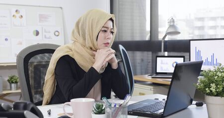 Foto de Frustrated tired arabic business woman reading document online with bad news on laptop. - Imagen libre de derechos