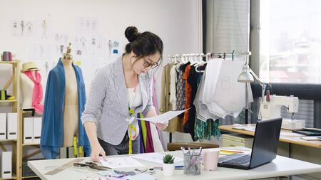 Photo for elegant female designer working on laptop and sketching at desk in studio. young woman fashion worker in workshop looking examining at paper of new collection checking with mannequin standing behind - Royalty Free Image